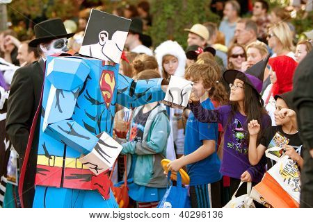 Superman Cartoon Character Fist Bumps Kids At Halloween Parade