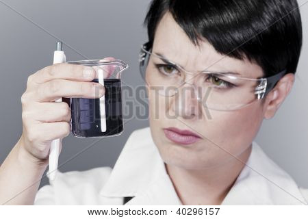 A female medical or scientific researcher or doctor looking at a liquid clear solution in a laboratory.