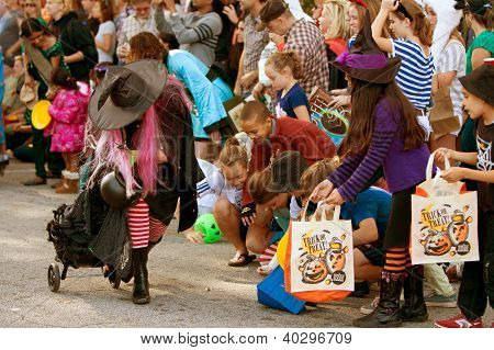Witch Hands Out Candy To Kids At Halloween Parade