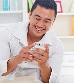 Cheerful Asian man using smartphone at home, looking on screen.