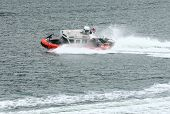 foto of coast guard  - Coast Guard boat cutting through water in harbor - JPG