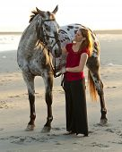 stock photo of appaloosa  - woman with her appaloosa horse on the beach - JPG
