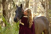 stock photo of bareback  - woman in medieval dress with horse in forest - JPG
