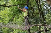 foto of preteen  - Preteen girl is climbing on the rope net at the ropes course - JPG