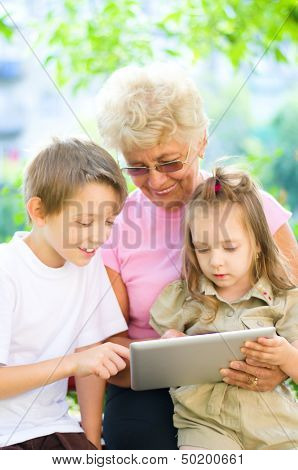 Grandmother With Grandchildren Using Tablet