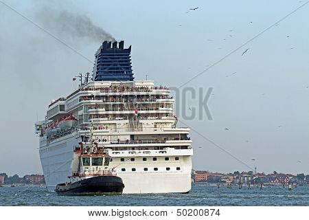 Tugboat While Accurately Manoeuvre The Large Cruise Ship Out Of The Port City