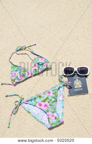 Passaporte, óculos de sol e biquíni