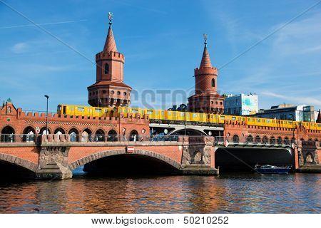 The Oberbaum Bridge, German Oberbaumbrucke and River Spree in Berlin, Germany. U-bahn going through the bridge