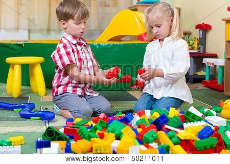 Two Children Playing With Blocks On The Floor