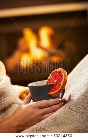 Having hot tea with blood orange in front of fireplace, female hand holding mug.