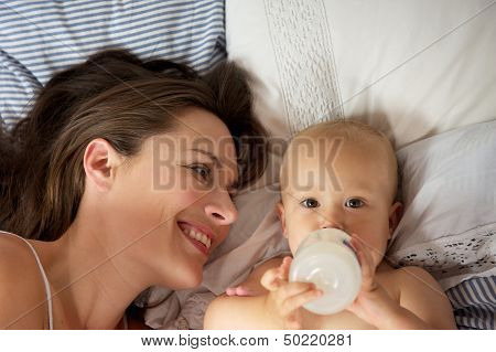 Portrait Of A Happy Mother With Cute Baby Drinking From Bottle