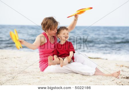 Young Happy Mother Playing With Her Son On The Beach
