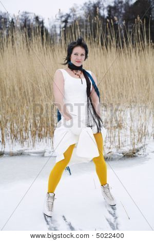 Woman Wearing A Stylish Dress, Scarf And Ice Skates Standing On A Frozen Lake.