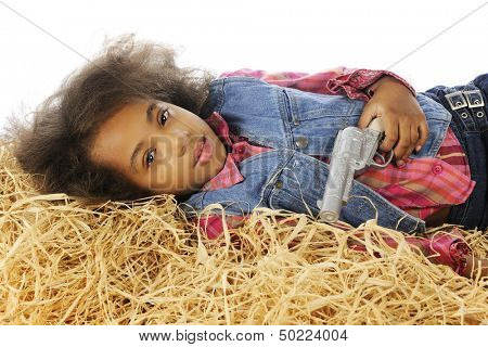 """A young sleepy-looking """"cowgirl"""" holding her gun across her chest while laying in the hay."""