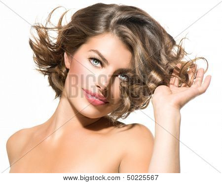 Beauty Young Woman Portrait over White Background. Beautiful Model Girl Touching Hair. Short Curly Hair, Fresh Clean Skin and Green Eyes. Hairstyle. Haircut