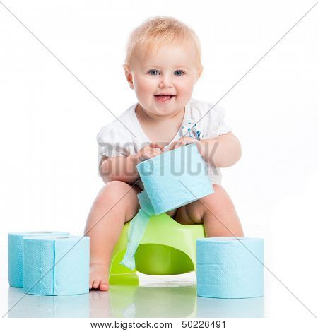 little baby sitting on a pot and keeps the toilet paper. studio photo on white background