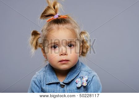 Disappointed little girl isolated on grey background