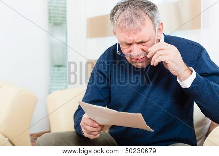 Older man or Senior have received a letter, maybe it's a reminder or a Bill