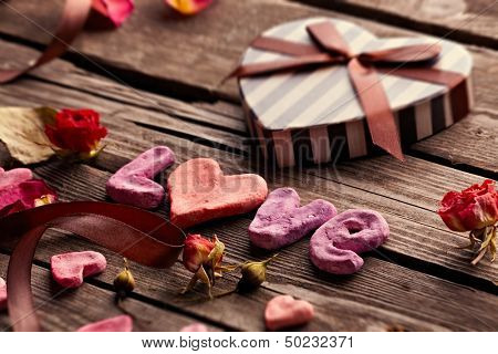 Word Love with heart shaped Valentines Day gift box on old vintage wooden plates. Sweet holiday background with rose petals and dried rose flowers.