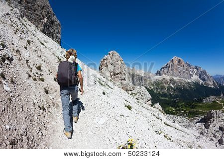 Young hiker walking on a mountain trail. Dolomities, South Tirol, italian Alps, Europe.