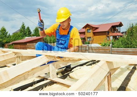 roofer carpenter worker nailing wood board with hammer on roof installation work