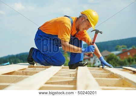 construction roofer carpenter worker nailing wood board with hammer on roof installation work