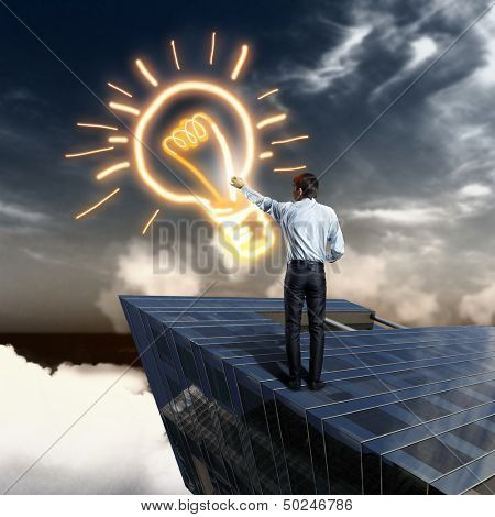 Image of young businessman drawing electric bulb
