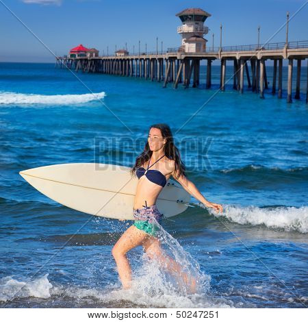 Brunette surfer girl running in Huntington Beach pier California [ photo-illustration]