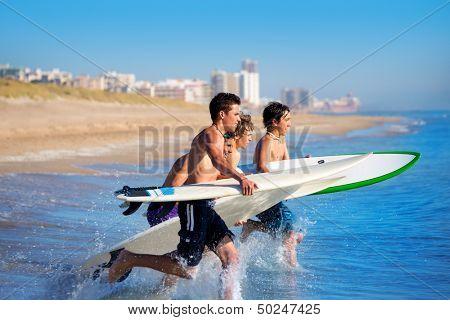 Teenager surfers surfing running jumping on surfboards at El Perello Cullera beach Spain