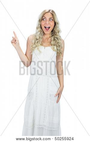 Astonished attractive model in white dress posing on white background