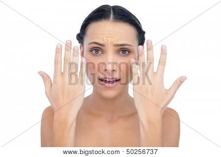 Annoyed natural model posing with hands up on white background