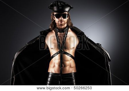 Portrait of a seductive handsome man wearing costume in police style.