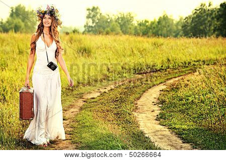 Romantic smiling young woman in a circlet of flowers goes on a country road with her old camera and suitcase.