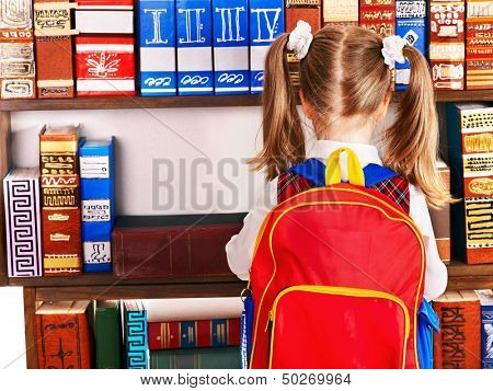Child with backpack reading book in library. Rear view.