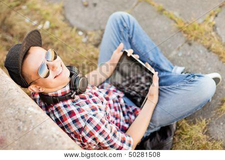 zomervakantie, tiener en technologie concept - tiener met hoofdtelefoons en tablet pc buiten