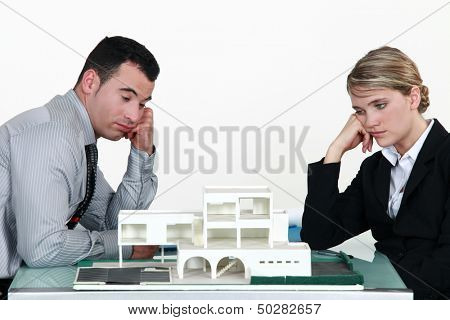 Two uninspired architects sat by model housing