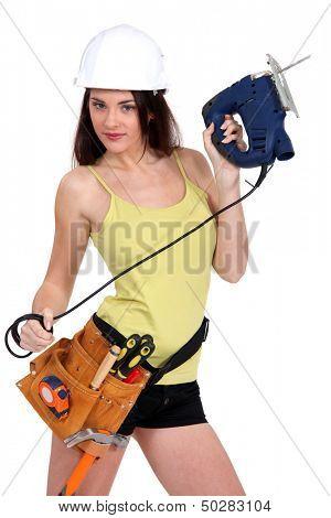Handywoman holding a jigsaw.