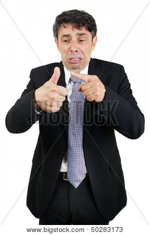 Tearful business man pointing to his injured thumb with a woeful piteous expression isolated on white
