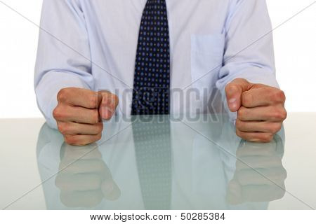 Male with fists on the table