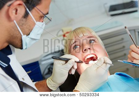 Dentist examining patient during dental treatment with probe and mirror