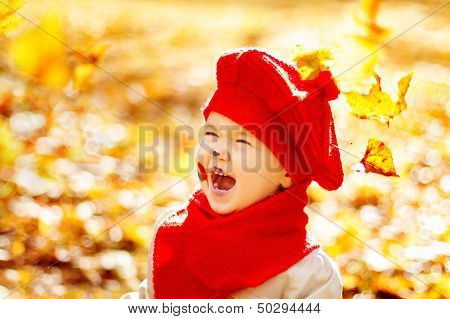 Happy Smiling Child In Yellow Autumn Park