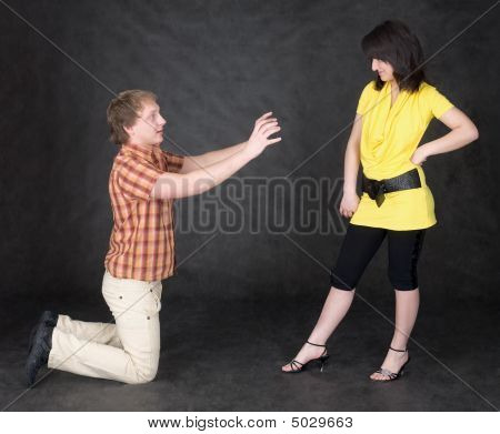 Man Is Kneeling To The Young Woman