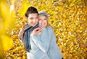 Happy couple have a romance in fall  branches of wood