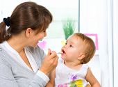 stock photo of porridge  - Mother Feeding Her Baby Girl with a Spoon - JPG