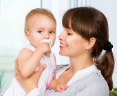 Mother and Baby kissing and hugging. Happy Family. Mother And Her Child with Pacifier at Home.