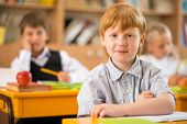 foto of redhead  - Little redhead schoolboy behind school desk during lesson - JPG