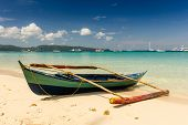 foto of camiguin  - A traditional style Bangca boat sits on the beach of a tropical island  - JPG