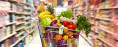 stock photo of supermarket  - Full shopping grocery cart in supermarket - JPG