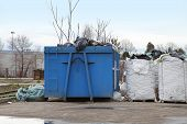 stock photo of dumpster  - Dumpster and bags of sorted material for recycling - JPG