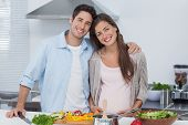 stock photo of pot-bellied  - Portrait of a man and his pregnant partner standing in the kitchen - JPG